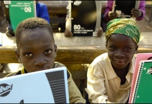 Kids with the donated Hilroy notebooks at their desks in the open air school